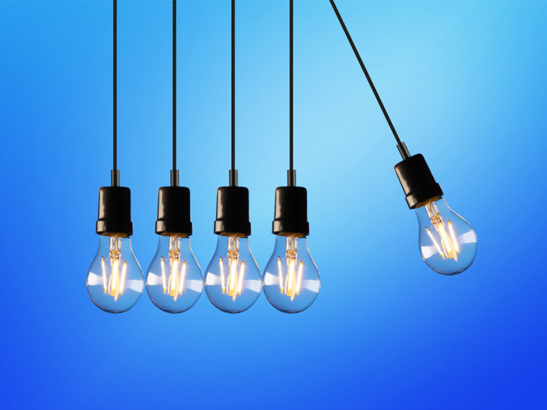 A row of lightlybulbs with the rightmost bulb about to swing into the others