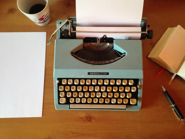 A typewriter and stationery on a desk as seen from above