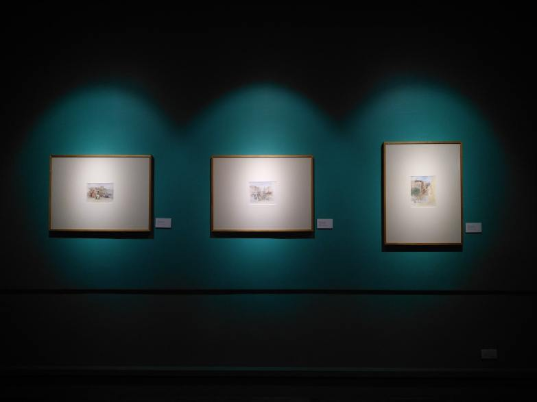Three pictures hanging in a gallery, illuminated by spotlights